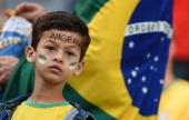 A young Nigerian fan is pictured in front of a Brazilian flag prior to a Group F football match between Iran and Nigeria at the Baixada Arena in...