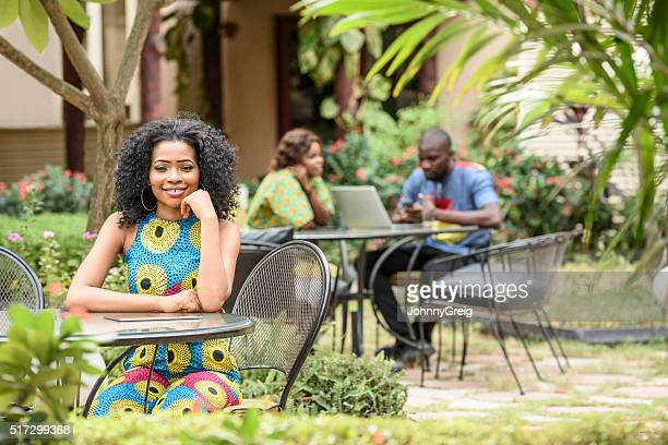 Young Nigerian woman sitting in garden cafe, smiling