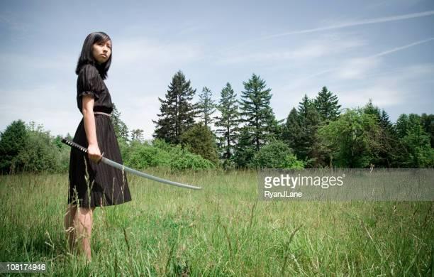 Young Ninja Warrior Girl In Field with Drawn Katana Sword