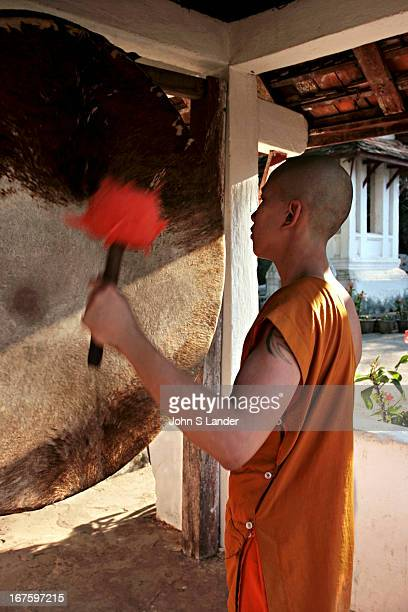 A young novice banging the temple drum at Wat Ban Sene in Luang Prabang while his friends man the gongs and bells