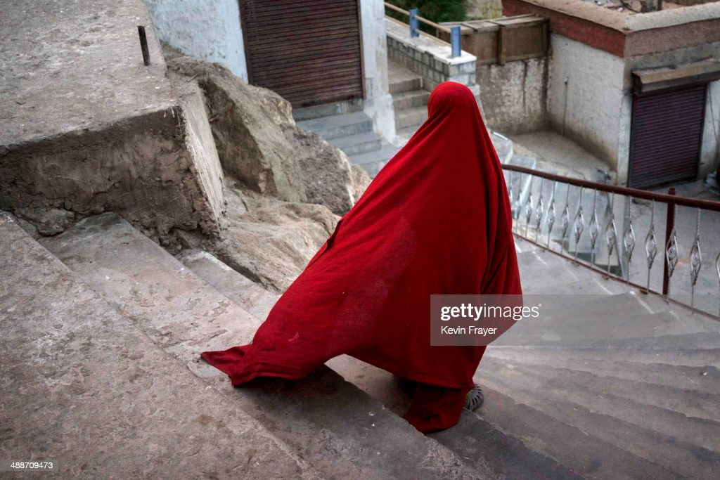 A young novice Buddhist monk puts on his robe as he walks down stairs after eating dinner at the Thiksey Monastery on May 7 2014 in Thiksey Ladakh...