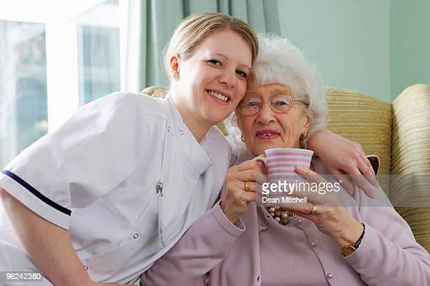 Jeune infirmière et une femme âgée câlins à un soin chez vous