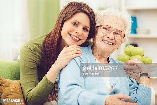 Young nurse embracing a happy senior woman