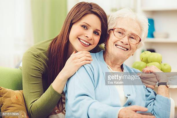 Young nurse embracing a happy senior woman
