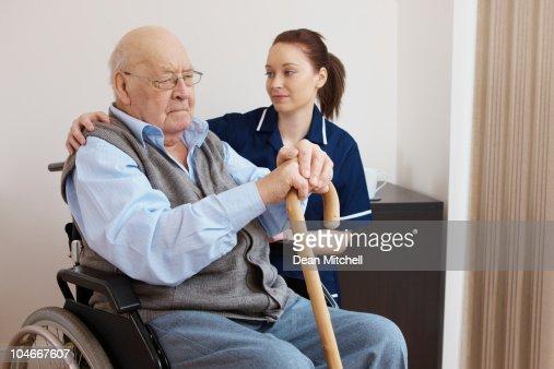 Giovane Infermiera Abbracciare Uomo Anziano In Sedia A