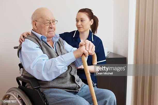 young nurse hugging senior man in wheelchair