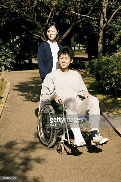 Young nurse pushing man patient in wheelchair