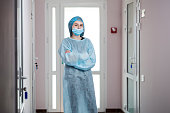 A young nurse stands in the corridor of a private clinic. The nurse is dressed in medical clothes for the operation.