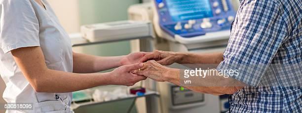 若い看護師の手を持つシニア女性の手