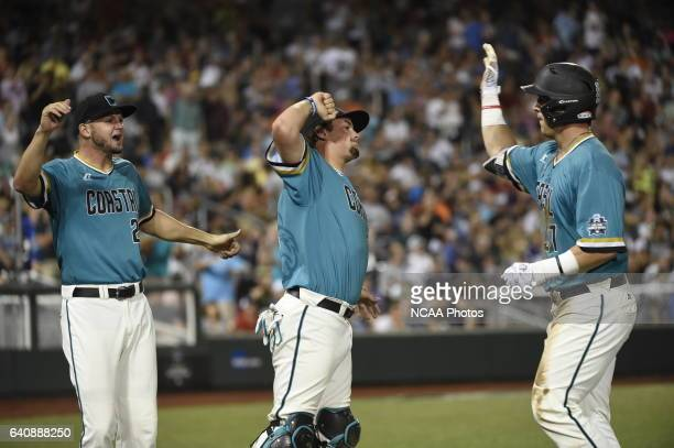 K Young of Coastal Carolina University drives in two runs with his hit and celebrates with teammates against the University of Arizona during the...