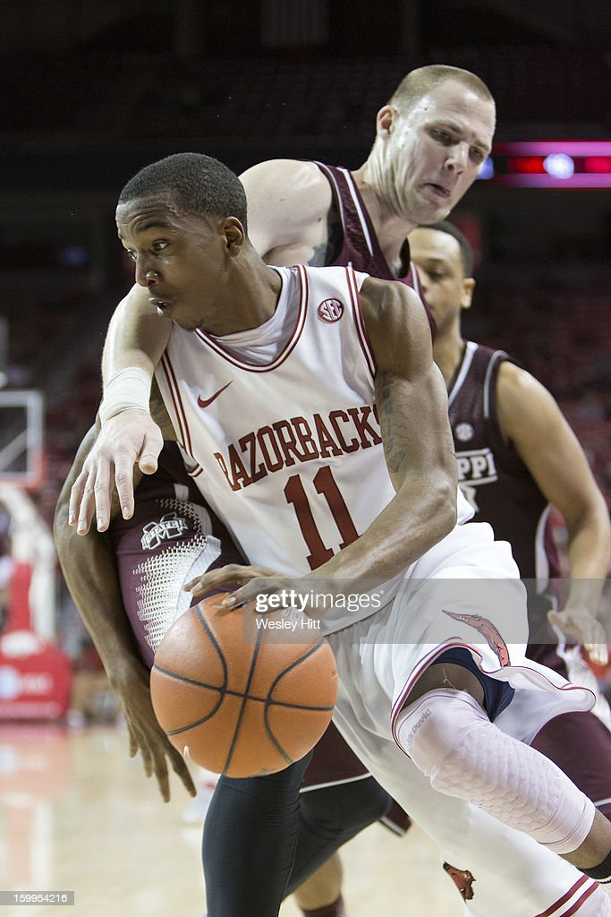 BJ Young #11 of the Arkansas Razorbacks drives around Colin Borchert #3 of the Mississippi State Bulldogs at Bud Walton Arena on January 23, 2013 in Fayetteville, Arkansas. The Razorbacks defeated the Bulldogs 96-70.