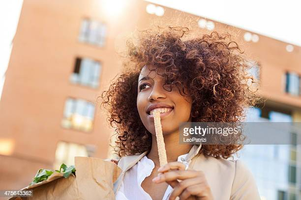 Young office worker in early morning eating a breadstick
