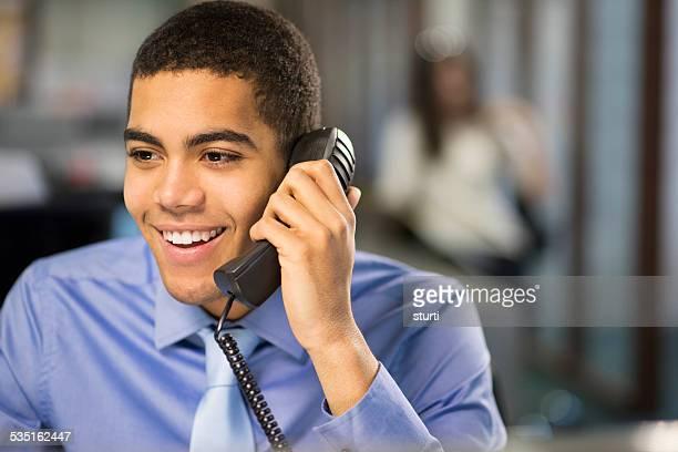 オフィスで働く若者の電話