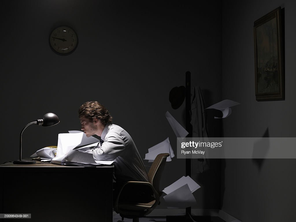 Young office worker sitting at desk, papers flying behind, side view : Stock Photo