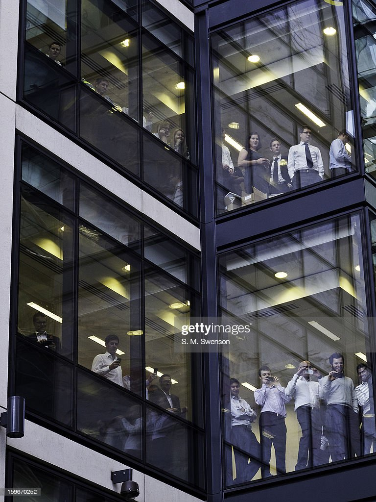CONTENT] Young office workers onlooking a student protest from a modern glass skyscaper. The protest was against the trebling of university fees that had passed the year before and government imposed austerity. Taken in the City of London (financial district) on the afternoon of November 9, 2011.