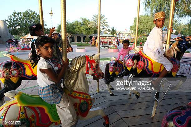 Young Omanis enjoy the day at an amusement park on the second day of the Eid alFitr in the capital Muscat on September 11 as Muslim families continue...