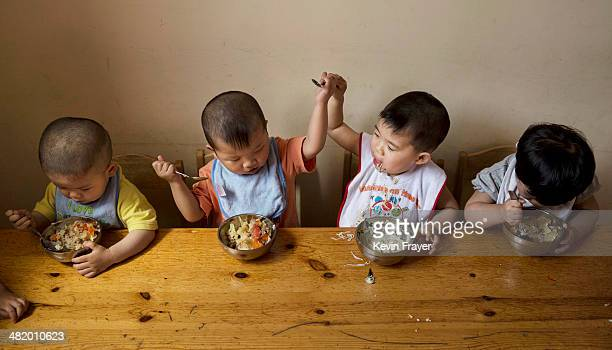 A young orphaned Chinese boy prevents another from taking some of his food as they eat a meal during feeding at a foster care center on April 2 2014...