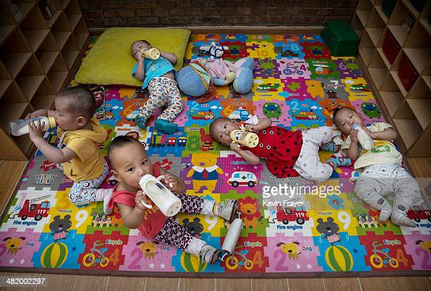 Young orphaned Chinese children drink milk from bottles at a foster care center on April 2 2014 in Beijing China China's orphanages and foster homes...