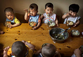 Young orphaned Chinese children eat a meal during feeding at a foster care center on April 2 2014 in Beijing China China's orphanages and foster...