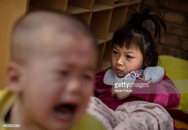 A young orphaned Chinese girl cries as she sits at a foster care center on April 2 2014 in Beijing China China's orphanages and foster homes used to...
