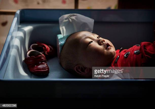 A young orphaned Chinese girl lays on a changing table at a foster care center on April 2 2014 in Beijing China China's orphanages and foster homes...