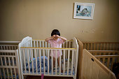 A young orphaned Chinese girl stands in a crib at a foster care center on April 2 2014 in Beijing China China's orphanages and foster homes used to...