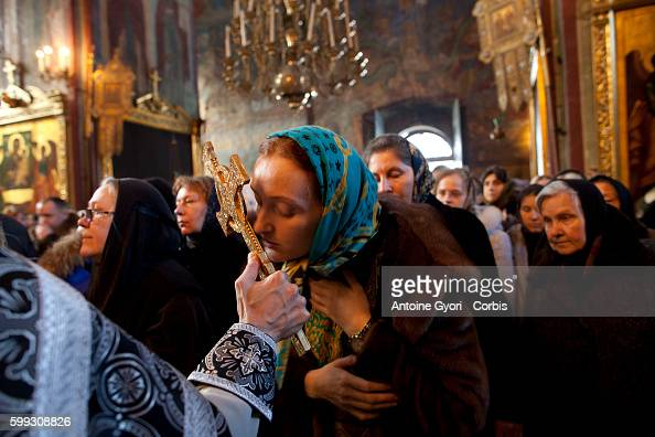 A young Orthodox woman delivers a kiss on the cross before receiving the Sacrament The Russian Orthodox Church is the main and semiofficial religion...