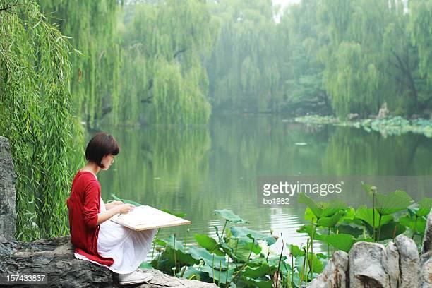 Jeune peintre assis près du lac