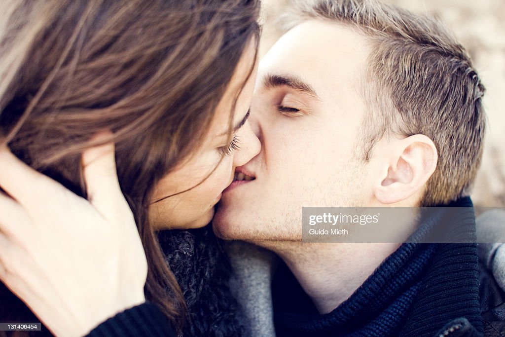 Young pair kissing in park : Stock Photo