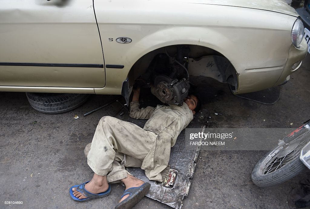 A young Pakistan car machanic works on a vehicle at a market in Rawalpindi on May 4, 2016. / AFP / FAROOQ