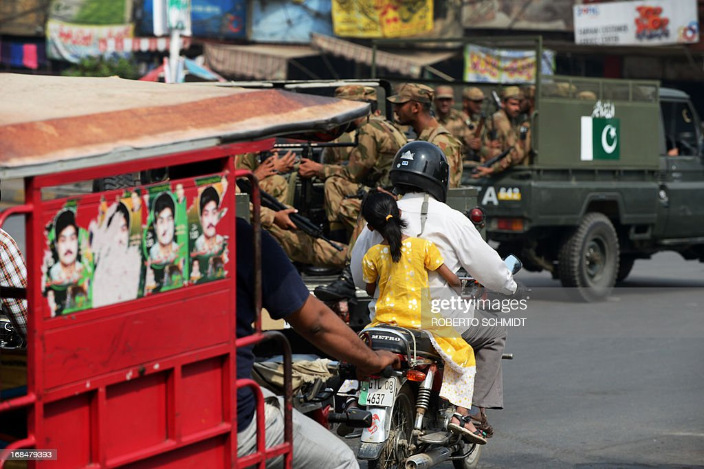 A young Pakistani child rides pillion on a motorcycle as army soldiers move in a convoy near the old city of Lahore on May 10, 2013, one day before some 86 million registered voters will go to the polls to elect lawmakers to the lower house of parliament and four provincial assemblies. Pakistan's general elections will mark the first democratic transition of power in the country's 66-year existence. The Pakistani authorities have deployed tens of thousands of personnel around the country in an effort to safeguard the election process which militant groups have vowed to disrupt. AFP PHOTOS/Roberto SCHMIDT
