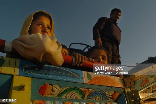 A young Pakistani girl and boy look on as an antinarcotics officer searches for drugs aboard a Pakistani vehicle that has been stopped by Her...