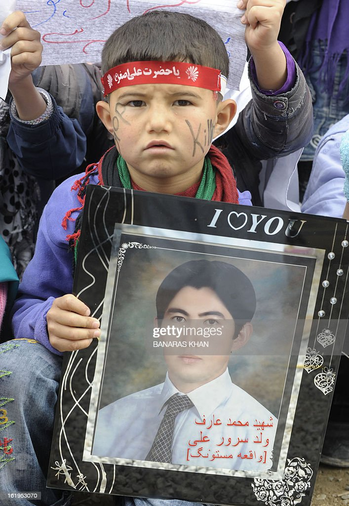 A young Pakistani Shiite Muslim boy looks on while holding a portrait of a slain relative on the second day of protests against a devastating bomb attack in Quetta on February 18, 2013. Thousands of women refused Monday to bury victims of a bloody bombing and a strike shut down Pakistan's biggest city Karachi as protesters across the country demanded protection for Shiite Muslims. AFP HOTO/Banaras KHAN