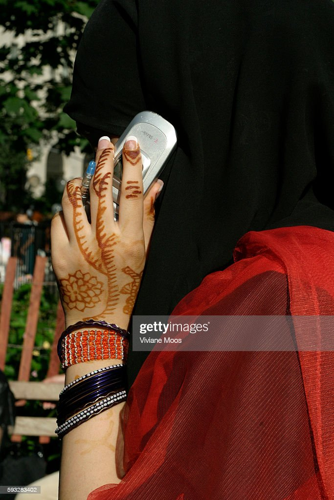 A young Pakistani woman's hennaed hands holding her cell phone accentuates the divide between her tradition and modern technology Model Release