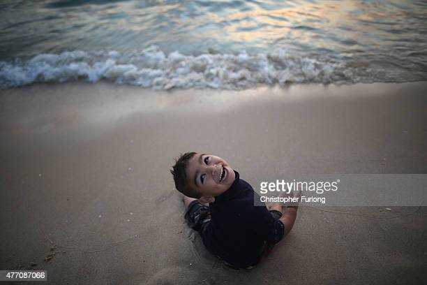 A young Palastinian boy laughs as the waves rush towards him on Gaza beach on June 13 2015 in Gaza City Gaza Palestinians are taking the opportunity...