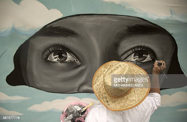 A young Palestinian artist takes part in the painting of a large mural on the wall of UNRWA compound in Gaza City on September 9 2015 during an...
