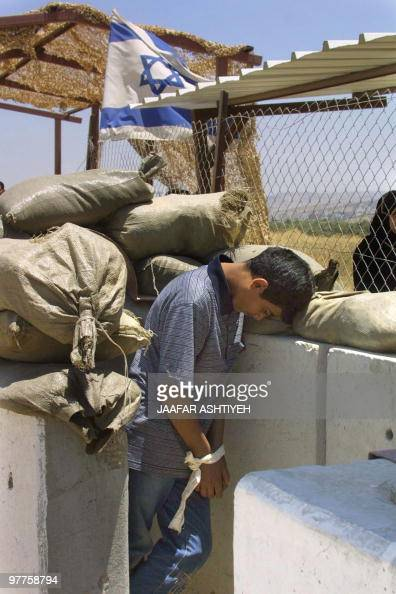 A young Palestinian boy stands handcuffed under an Israeli flag at the army checkpoint of Hawara in the West Bank south of Nablus 09 June 2003 Israel...