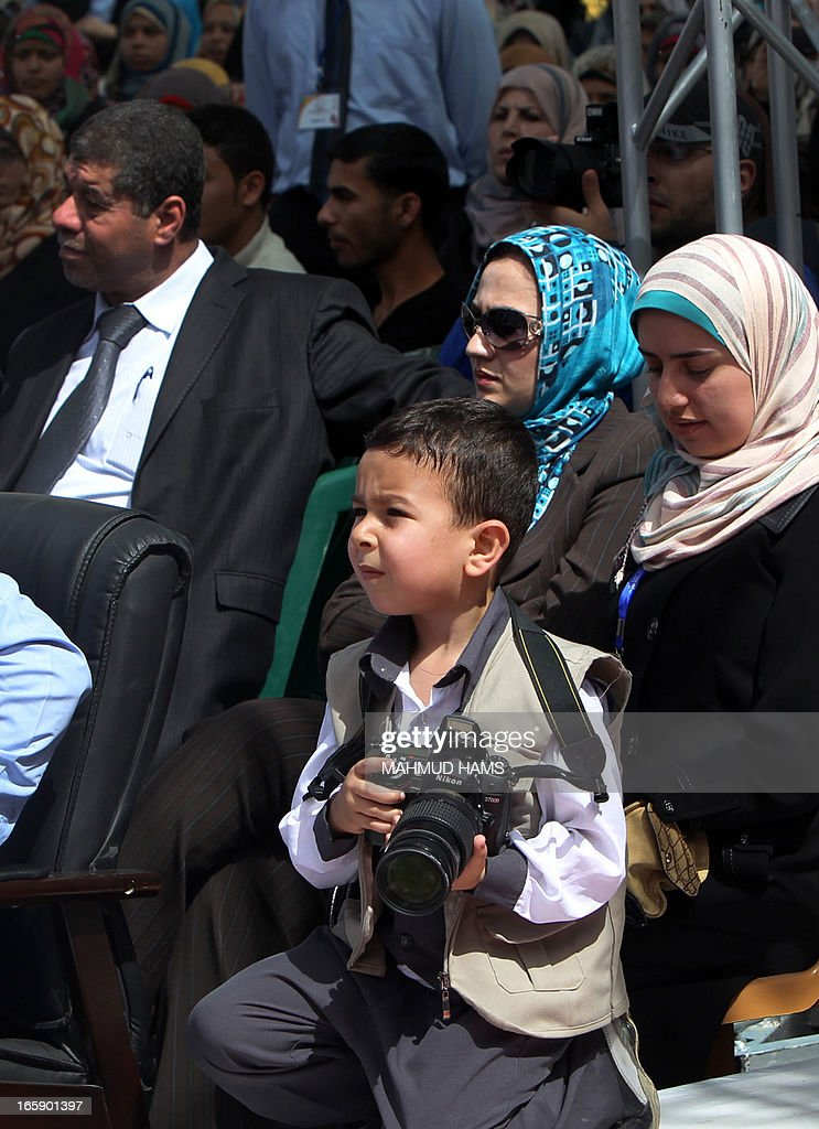 A young Palestinian boy takes holds a camera during the Children's Fund festival at the Community College of the Islamic University of Gaza in Gaza city on April 7, 2013.