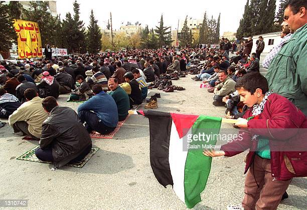 A young Palestinian boy unrolls the Palestinian flag during a sitin demonstration marking the anniversary of the first uprising against Israel...