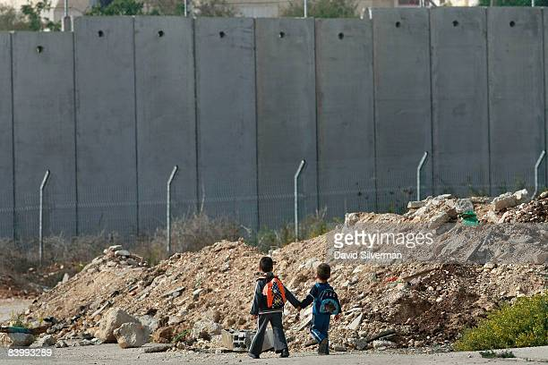 Young Palestinian boys walk home from school on what was once a major road from Israel into the West Bank until the Jewish State built it's...