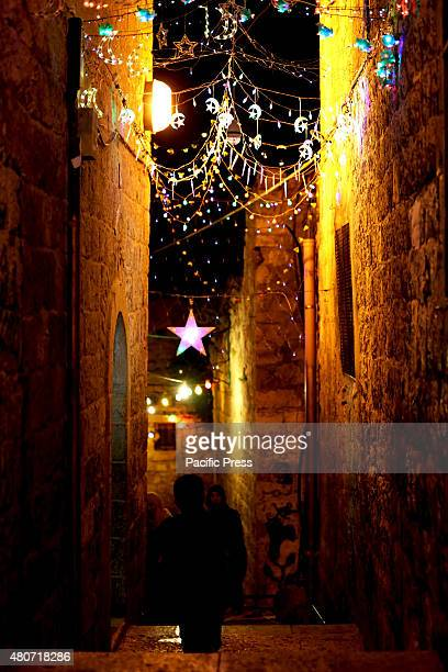 A young Palestinian child stands in a brightly lit street in the old city of Eastern Jerusalem on the night of Laylat Al Qadr In the last week of...
