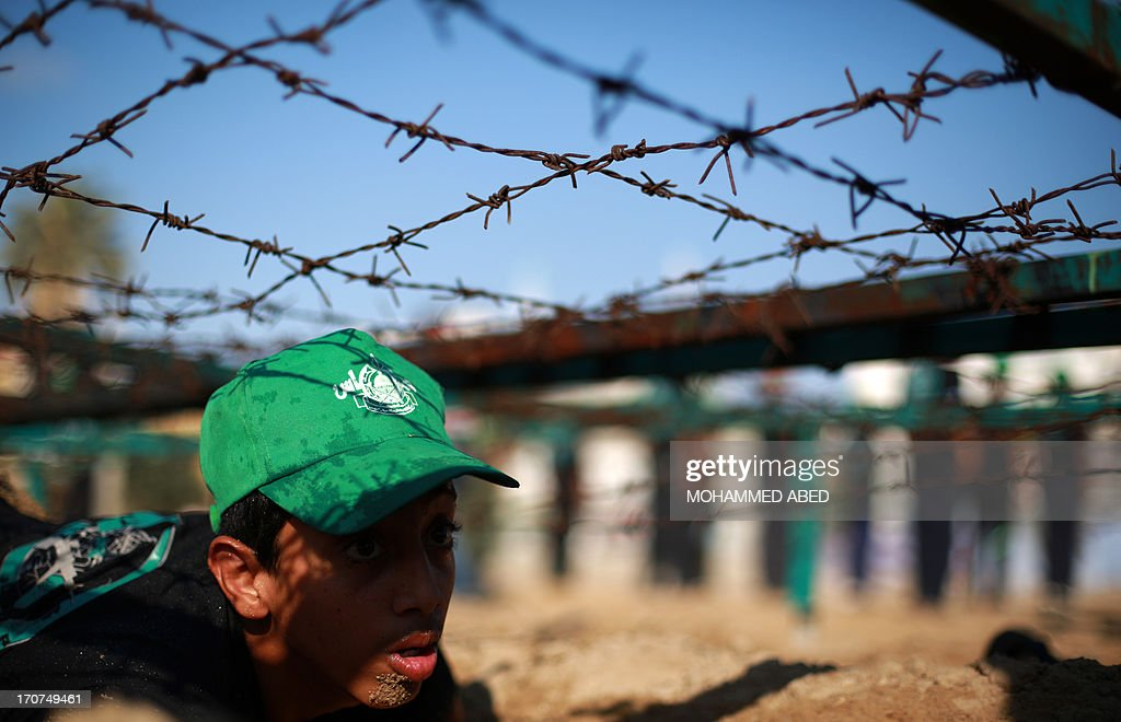 A Young Palestinian crawls under barbed-wire during a summer physical training camp run by Hamas in Gaza City on June 17, 2013.