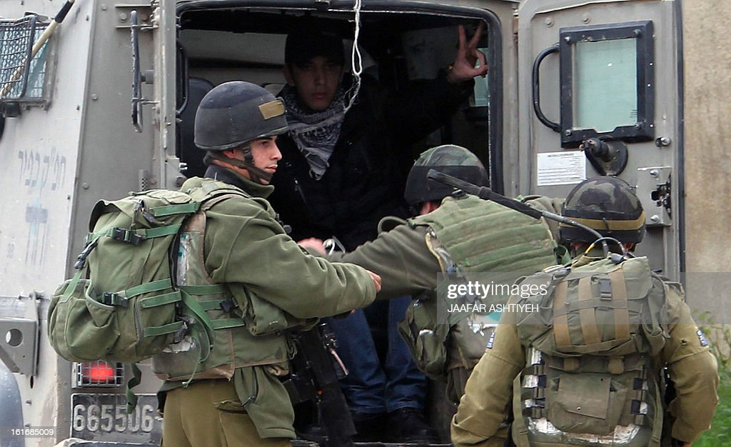 A young Palestinian flashes the sign of victory after being arrested by Israeli soldiers following clashes during a demonstration in support with Palestinian prisoners jailed in Israeli prisons on February 14, 2013 in Nablus, in the occupied West Bank.