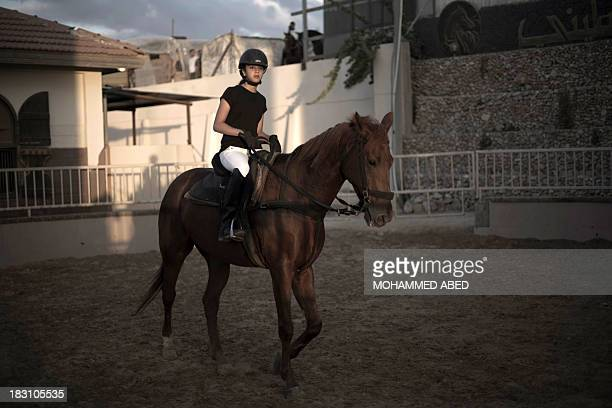 A Young Palestinian girl takes part in a horseback riding competition in Gaza City on October 4 2013 AFP PHOTO / MOHAMMED ABED