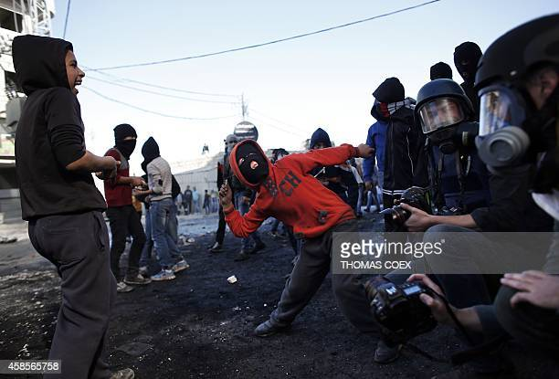 A young Palestinian hidding his face throws stones next to photographers during clashes with Israeli security forces in the Palestinian refugee camp...