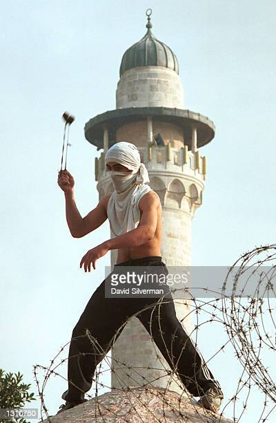 A young Palestinian man uses a slingshot to hurl stones at Israeli police December 8 2000 during violent clashes in the Old City of Jerusalem Israel...