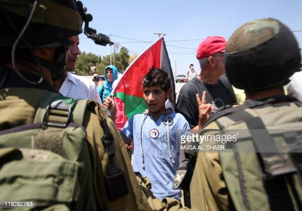 A young Palestinian protester holding his national flag flashes the 'V' for victory sign in front of Israeli soldiers during a demonstration against...