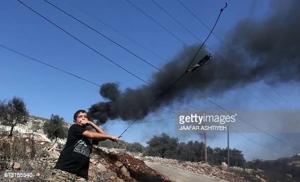 A young Palestinian protester uses a slingshot to throw stones towards Israeli security forces during clashes following a weekly demonstration...