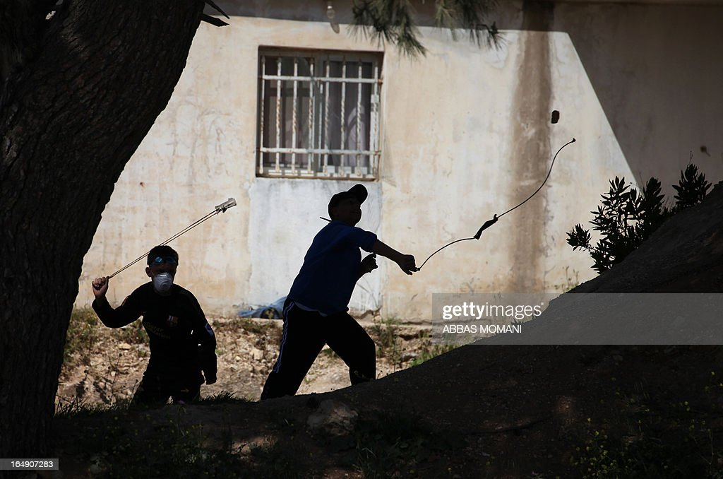 Young Palestinian protesters use slingshots to hurl stones towards Israeli troops during a demonstration against the expansion of Jewish settlements in the village of Nabi Saleh in the occupied West Bank on March 29, 2013.