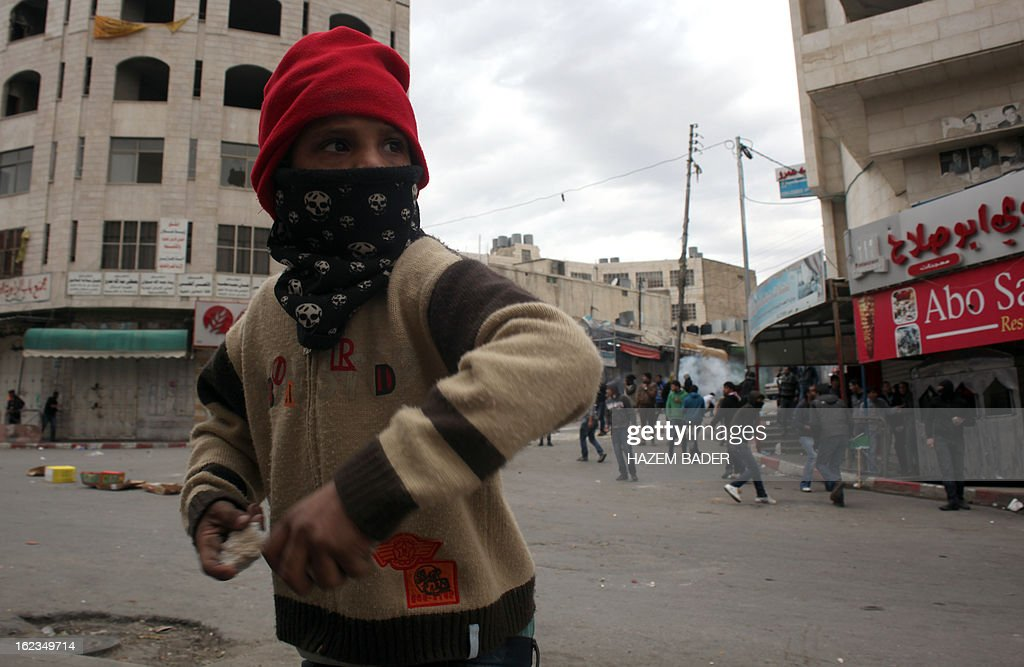 A young Palestinian protestor hurls a rock at Israeli border guards in al-Shuhada street in the West Bank town of Hebron on February 22, 2013 during a protest demanding the right of access for Palestinians to the street that can only be used by Israeli settlers. AFP PHOTO / HAZEM BADER